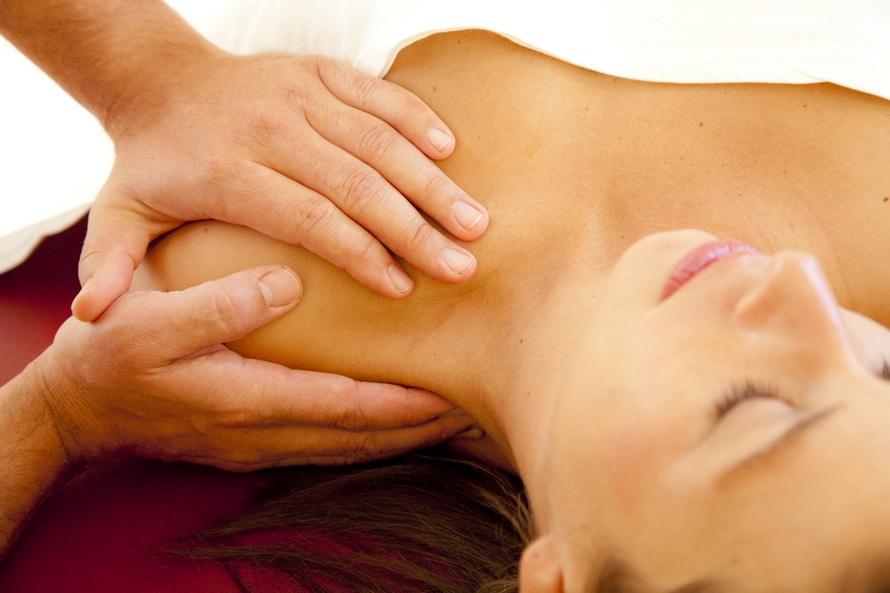 good looking woman receives a massage at her shoulder